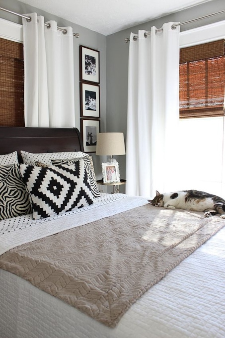 Bedroom with cozy linens and a cat asleep on the bed