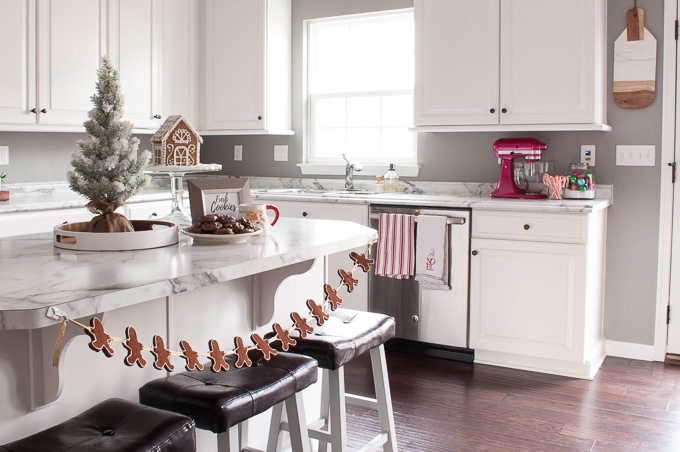 Modern meets Traditional Christmas Home Tour. This pretty white kitchen looks like a whimsical Christmas bakery. Check out the beautiful all white gingerbread house!