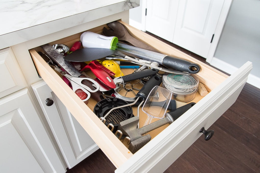 messy cluttered kitchen drawer with tools