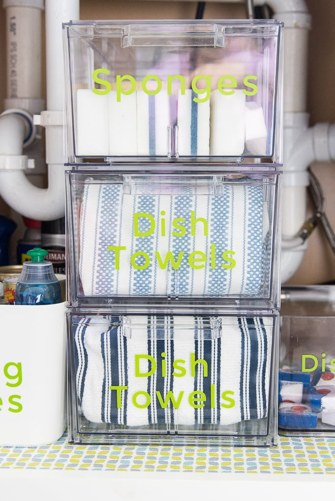 stacked clear organizing drawers under a kitchen sink with towels and sponges