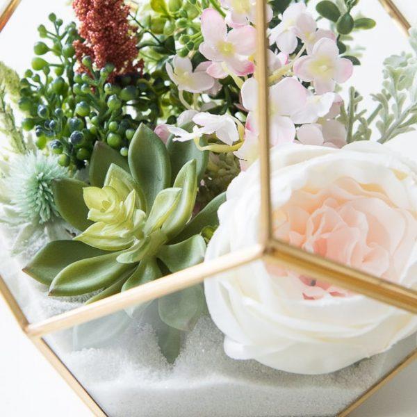 floral items in a gold terrarium