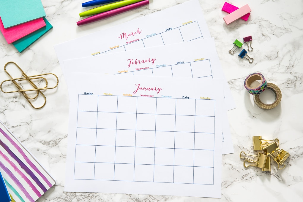 three months of printable calendars on a desk with office supplies
