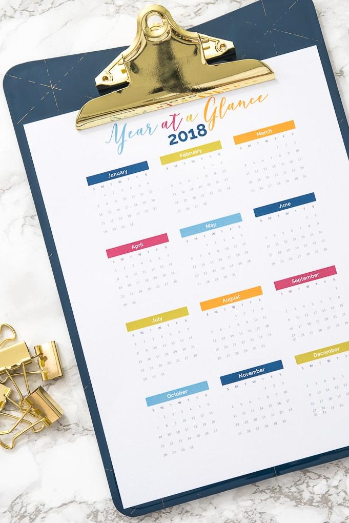 2018 year at a glance calendar on a blue clipboard on a desk