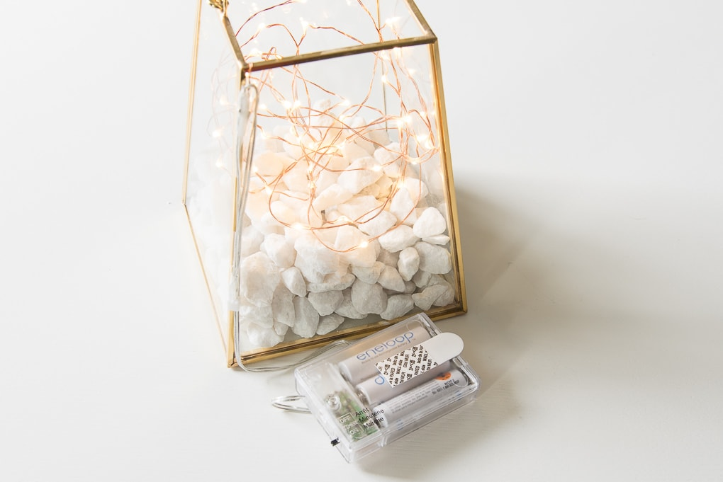 gold terrarium with fairy lights battery pack on a table
