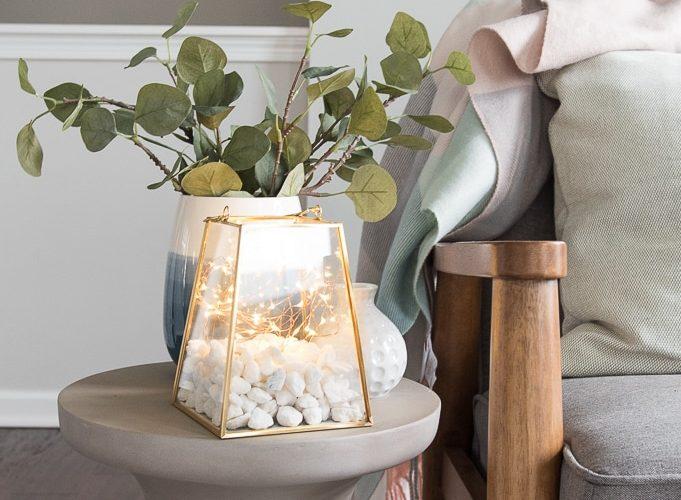 gold lantern terrarium with fairy lights on a table