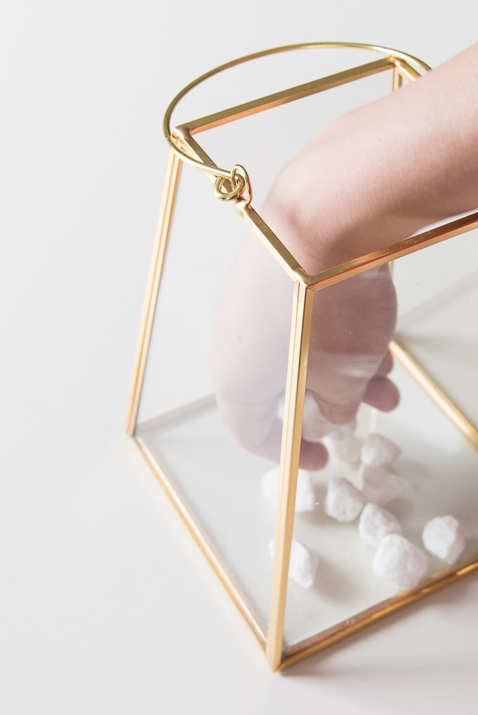 gold lantern terrarium with white rocks