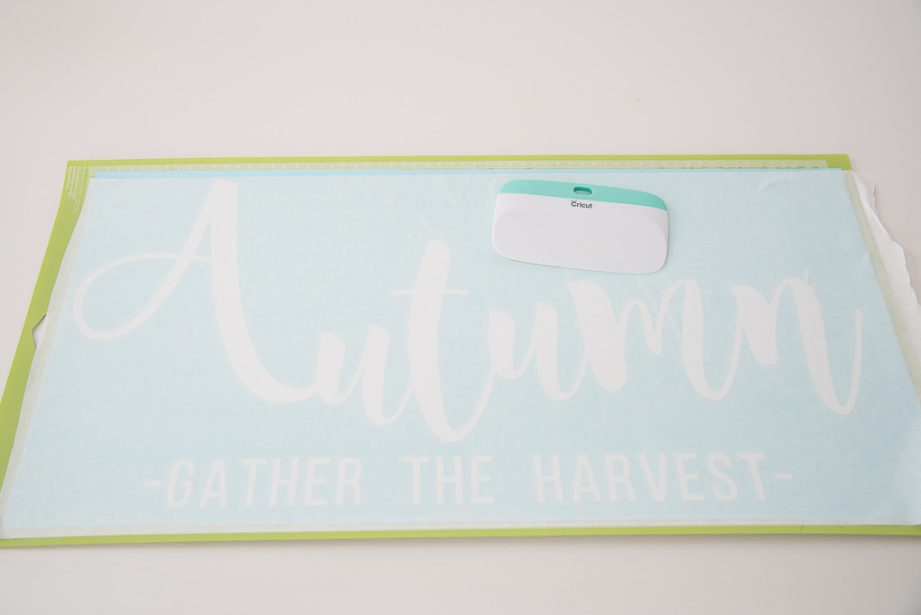 Cricut cutting mat with white vinyl and scraper tool