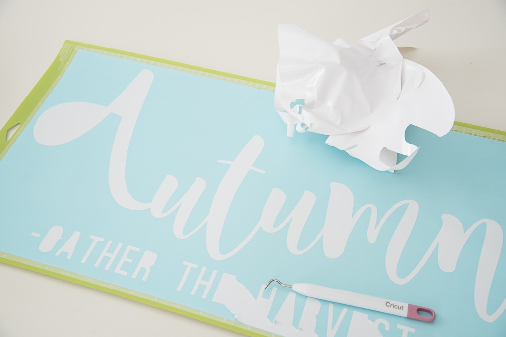 Cricut cutting mat with a white vinyl Autumn cutout design weeding process
