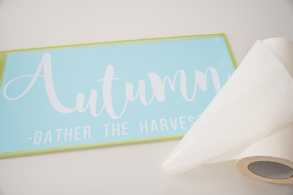 Cricut cutting mat with white vinyl design and transfer tape