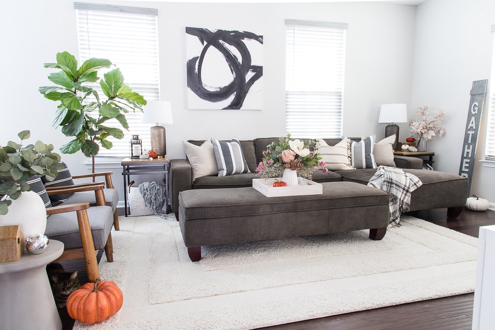 fall living room with blue and neutral throw pillows and a faux floral arrangement