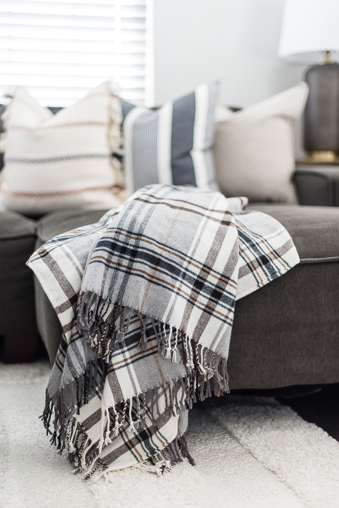 gray and white plaid throw blanket on a couch