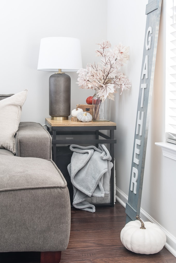 end table in living room with fall decorations and pink leaves