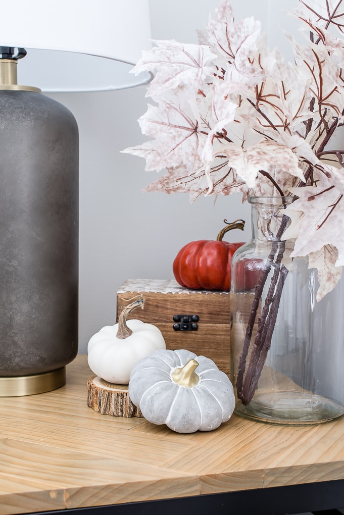 white gray and orange pumpkins on an end table for fall