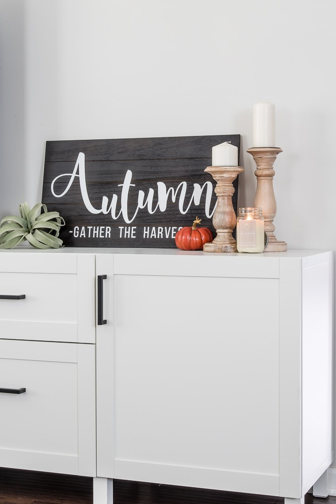 black and white wooden autumn sign on a white cabinet