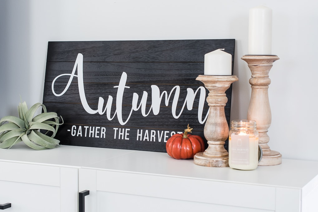 black and white wooden autumn sign with an orange pumpkin and natural wood candle holders
