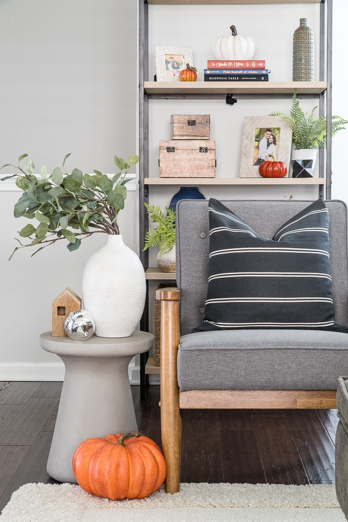 accent chair and side table with a white vase and eucalyptus and orange pumpkin