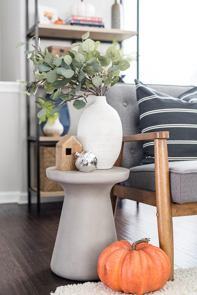 side table vignette white vase eucalyptus and orange pumpkin
