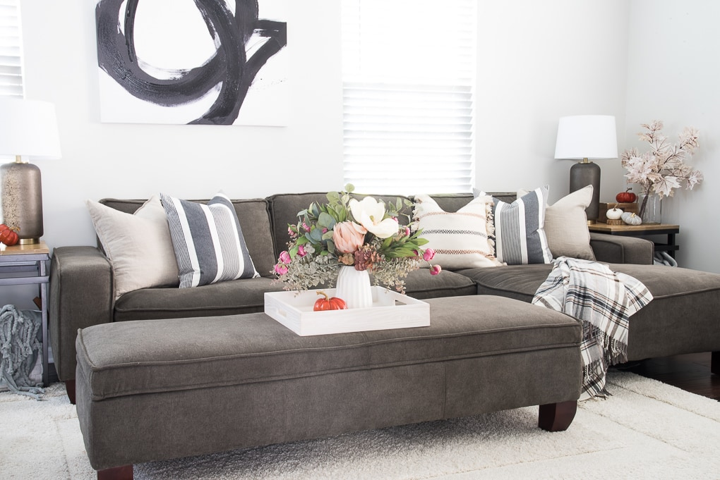 faux floral arrangement for fall on a tray on a couch with blue and neutral throw pillows