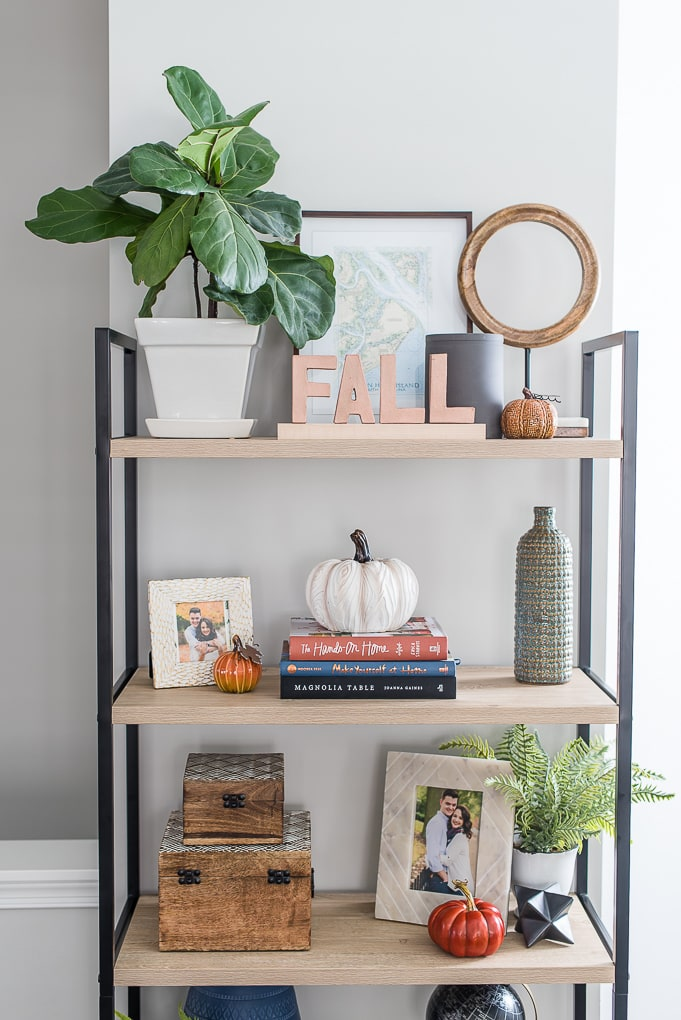natural wood bookshelf with fall decorations on the shelves