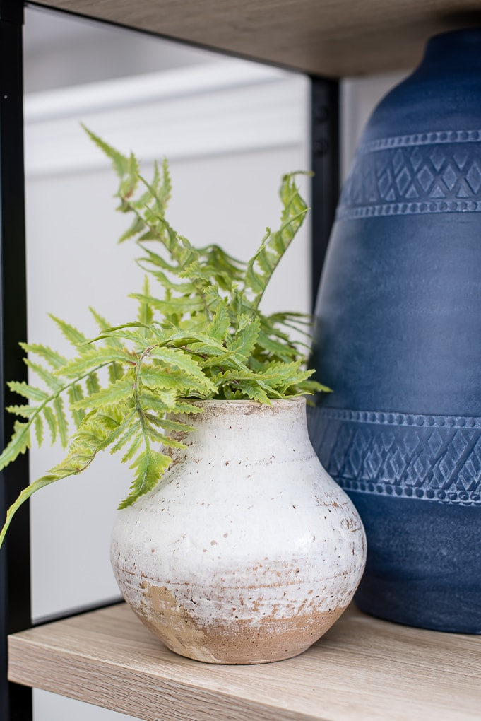 green faux floral stem in a natural clay vase on a bookshelf
