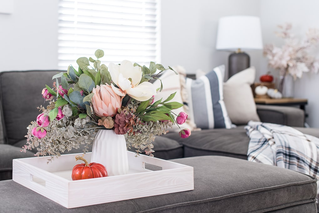 fall floral arrangement in white vase with couch and throw pillows neutral