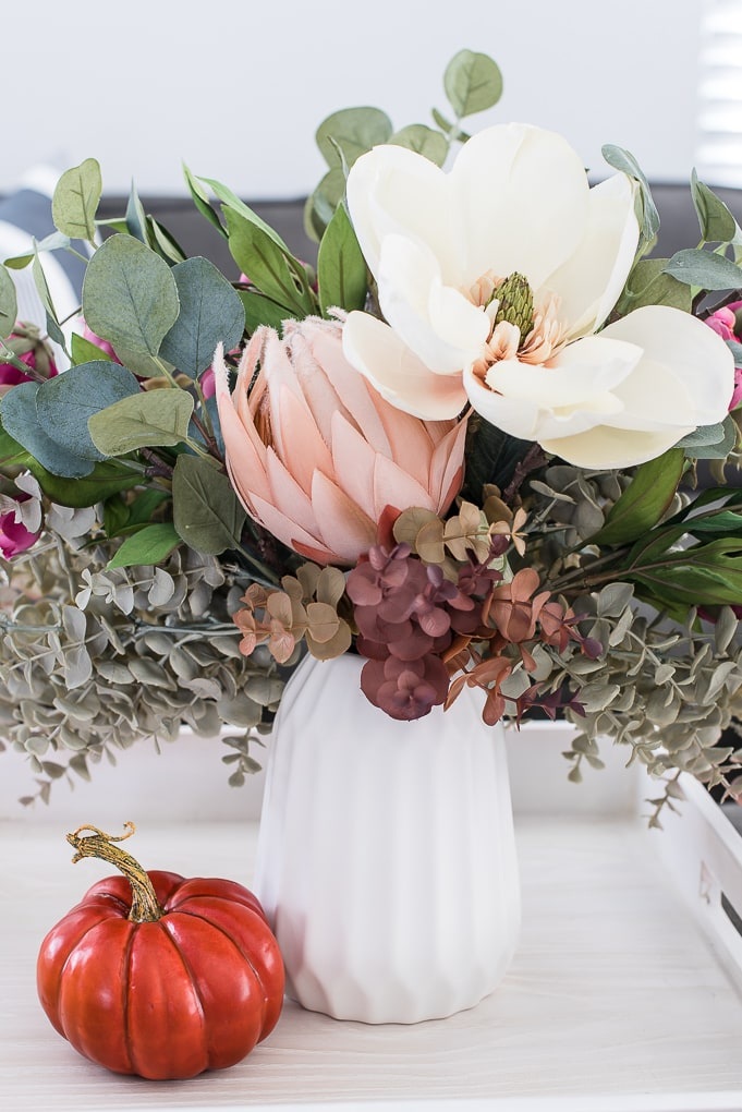 fall floral arrangement in a white vase with an orange pumpkin