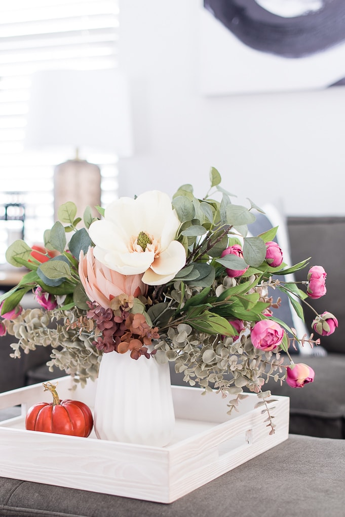 fall floral arrangement in a white vase on a tray with an orange pumpkin