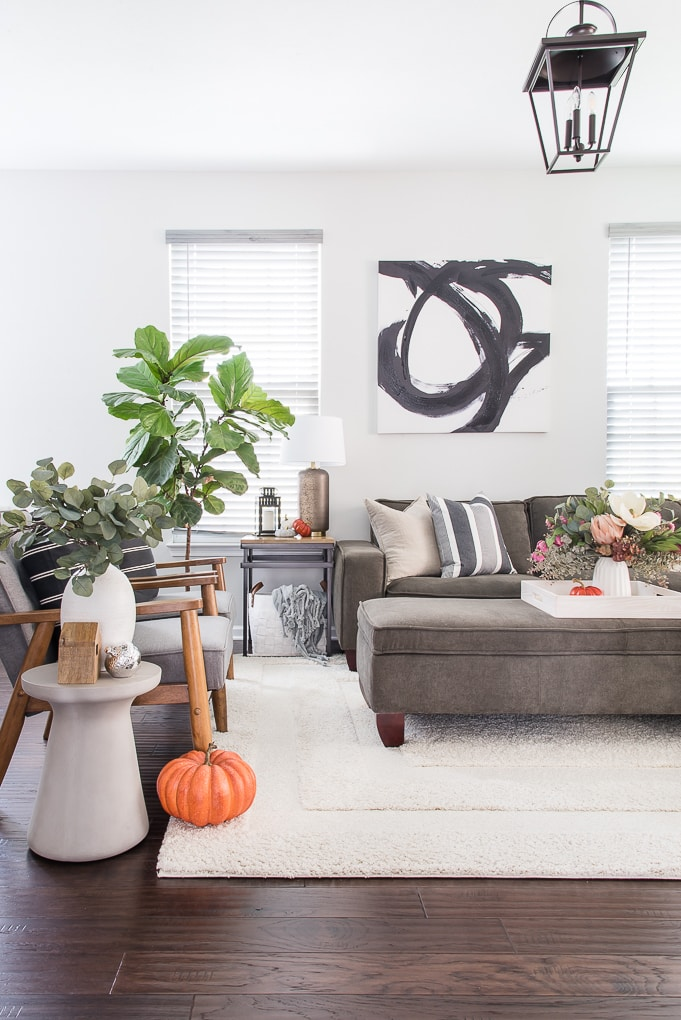 fall living room with blue and neutral throw pillows and orange pumpkin