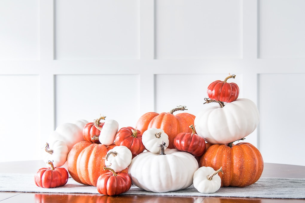 orange and white pumpkin pile centerpiece on a table