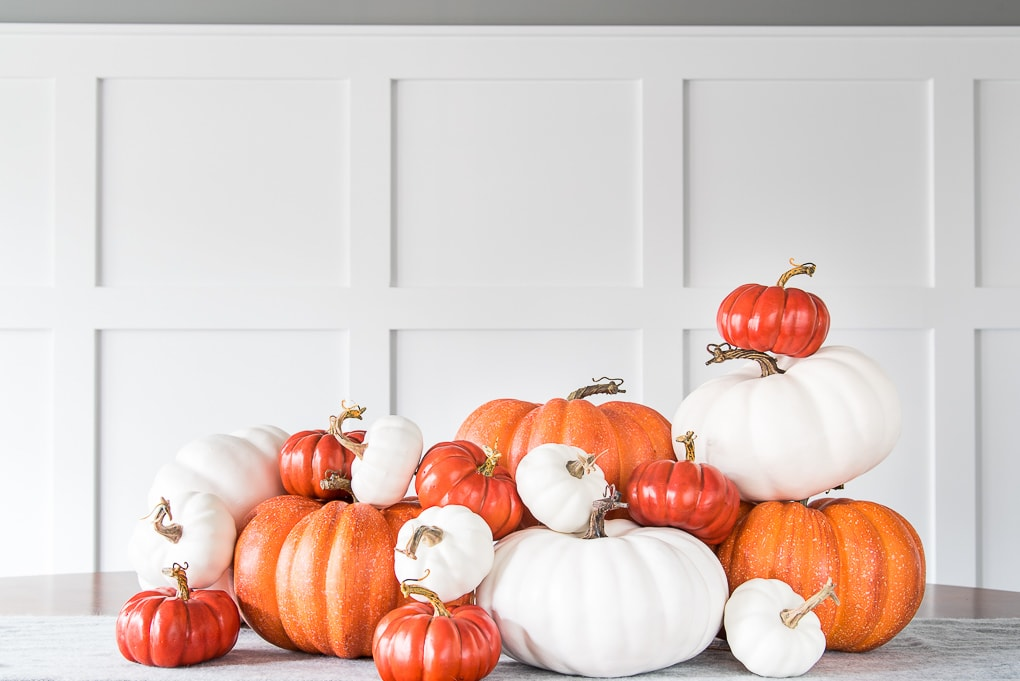 pile of orange and white pumpkins on a table