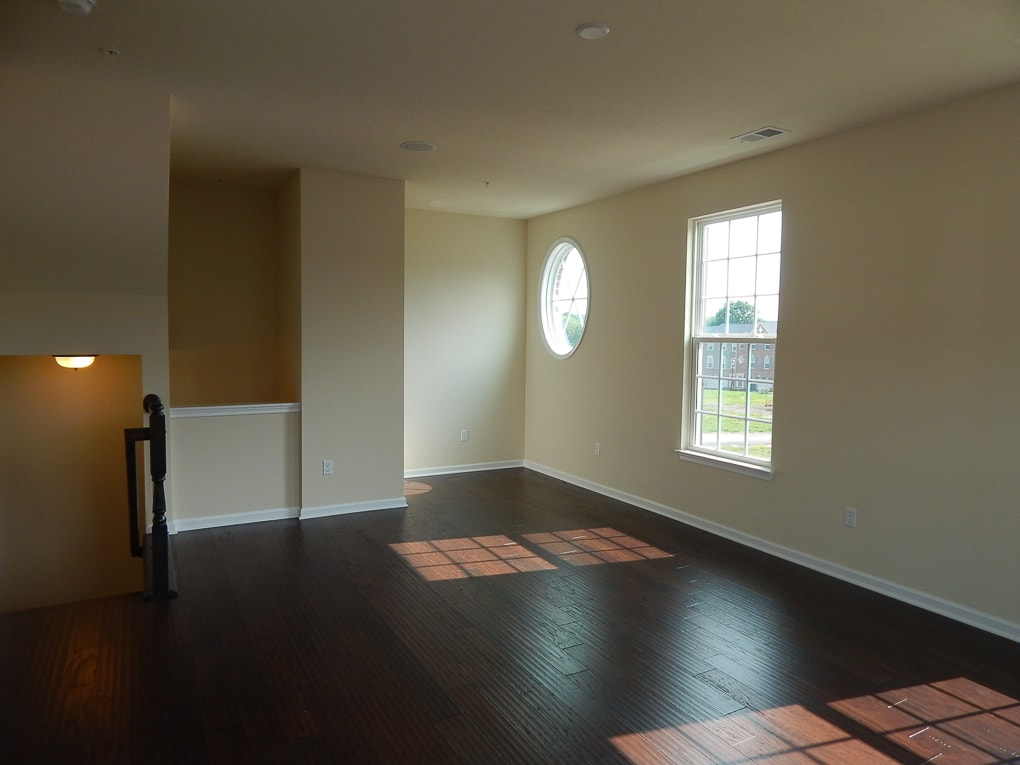 yellow empty living room builder grade home