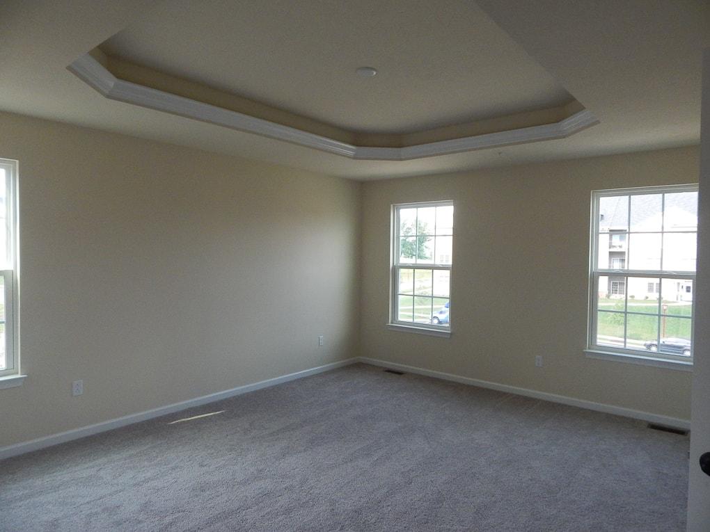 yellow empty master bedroom builder grade room
