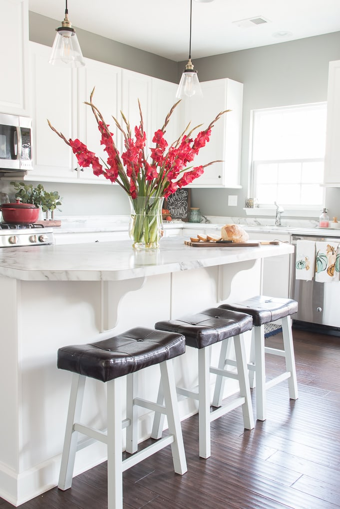 bright white kitchen with pink flowers on the island