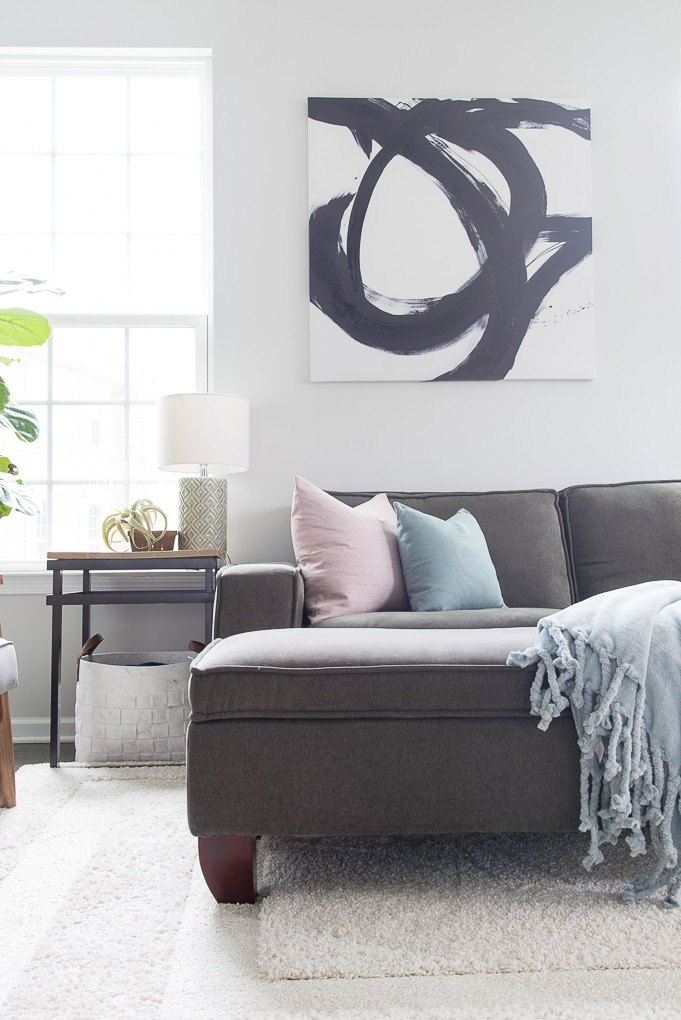 bright living room with gray couch throw pillows and blanket