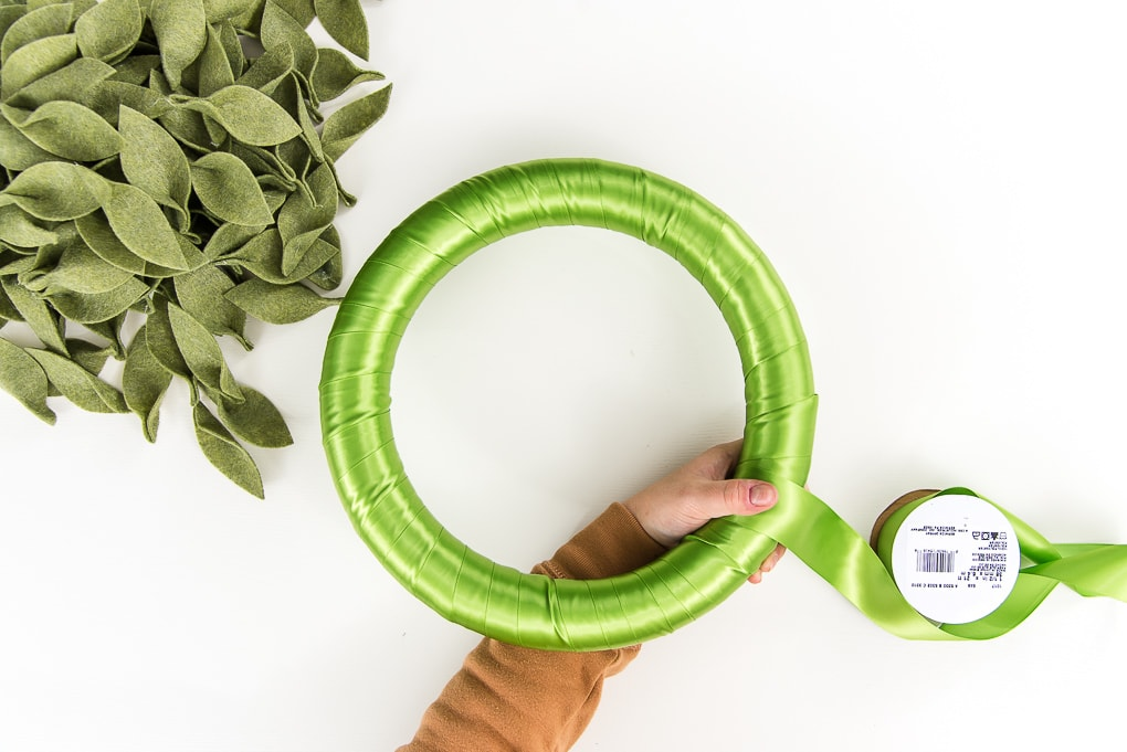 finishing wrapping green ribbon around a green wreath form