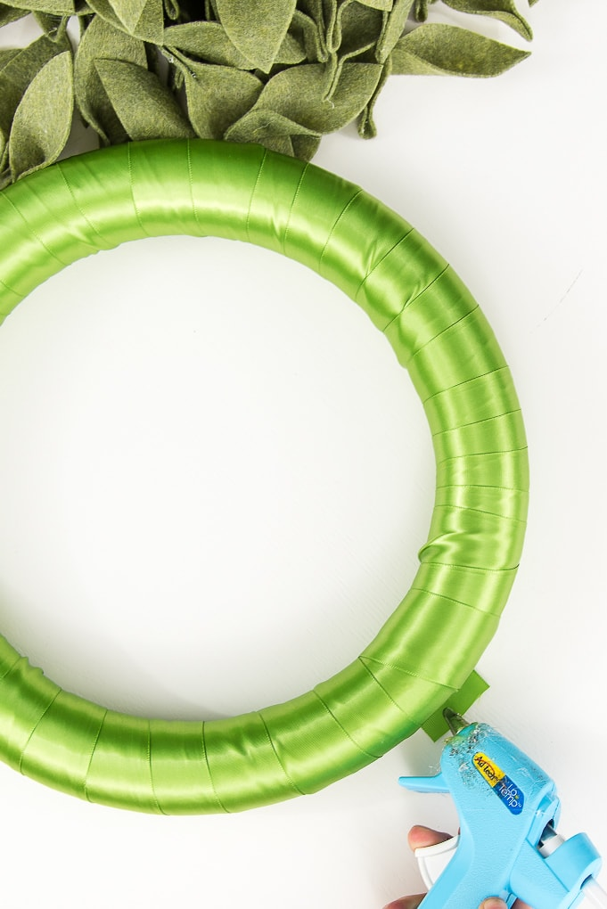 hot gluing green ribbon to wreath form