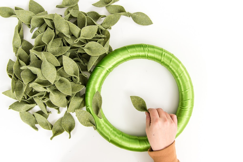 attaching green felt leaves to a wreath form