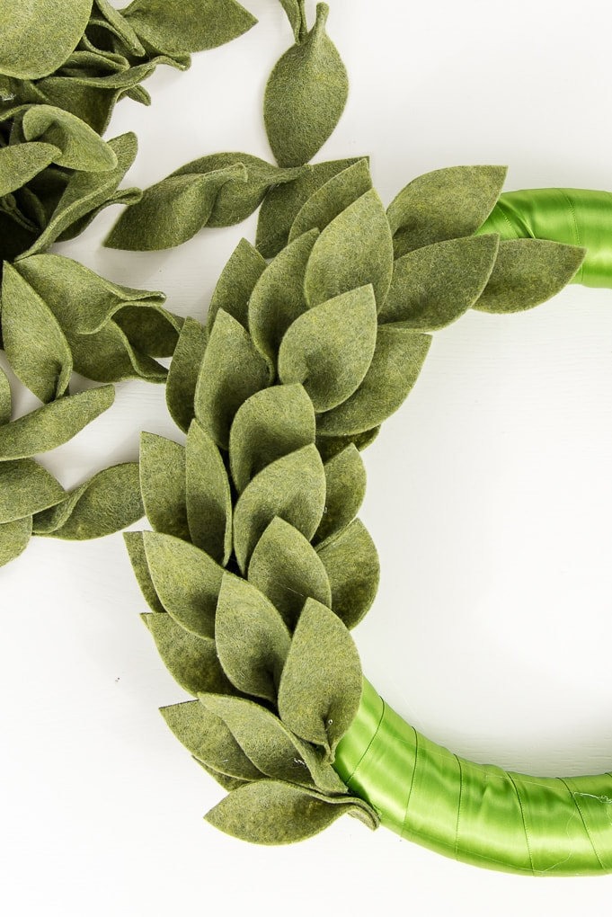 close up of green felt leaves on a wreath form
