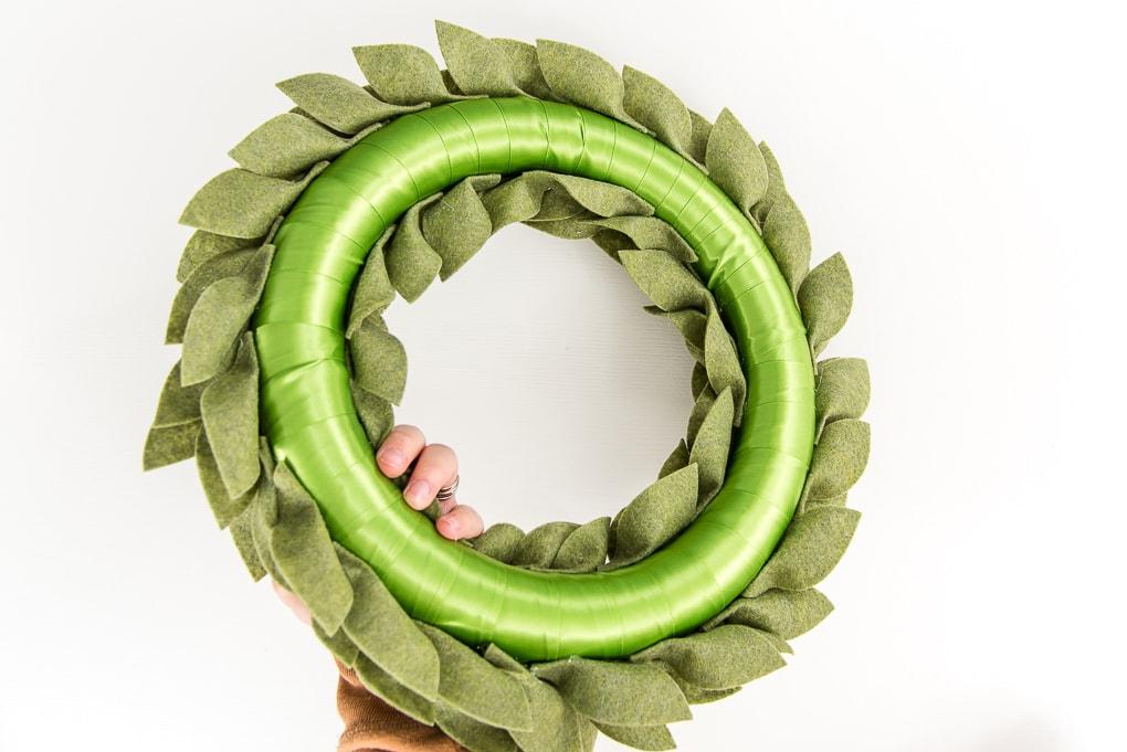 back of green felt greenery wreath with hand