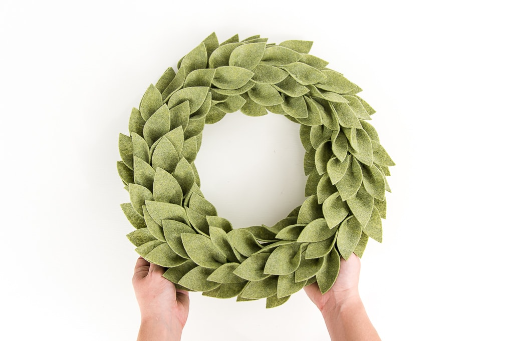 olive green felt greenery wreath being held by two hands
