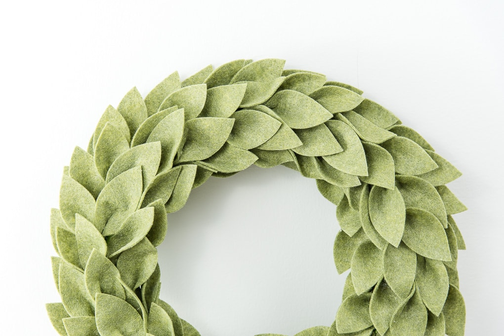 close up of olive green felt greenery wreath on table Christmas