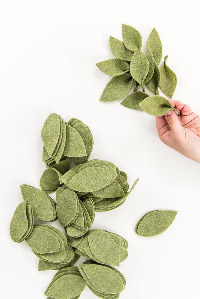hand assembling green felt leaves