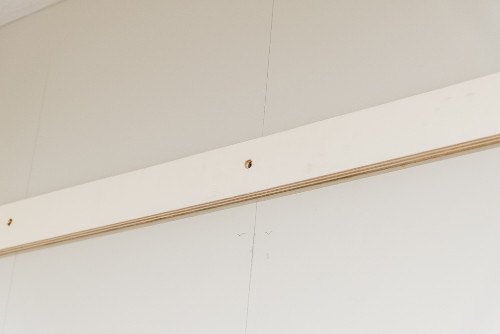 piece of wood attached to a wall with screws