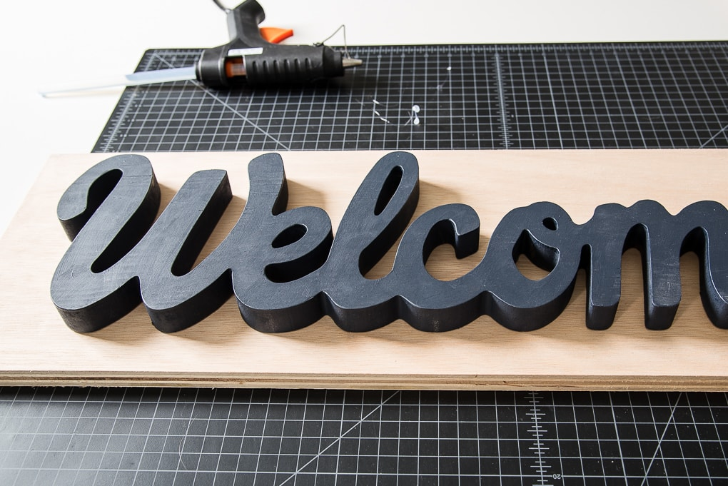 welcome wooden sign being glued to a piece of wood