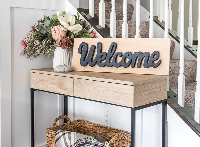 console table with wooden welcome sign and floral arrangement