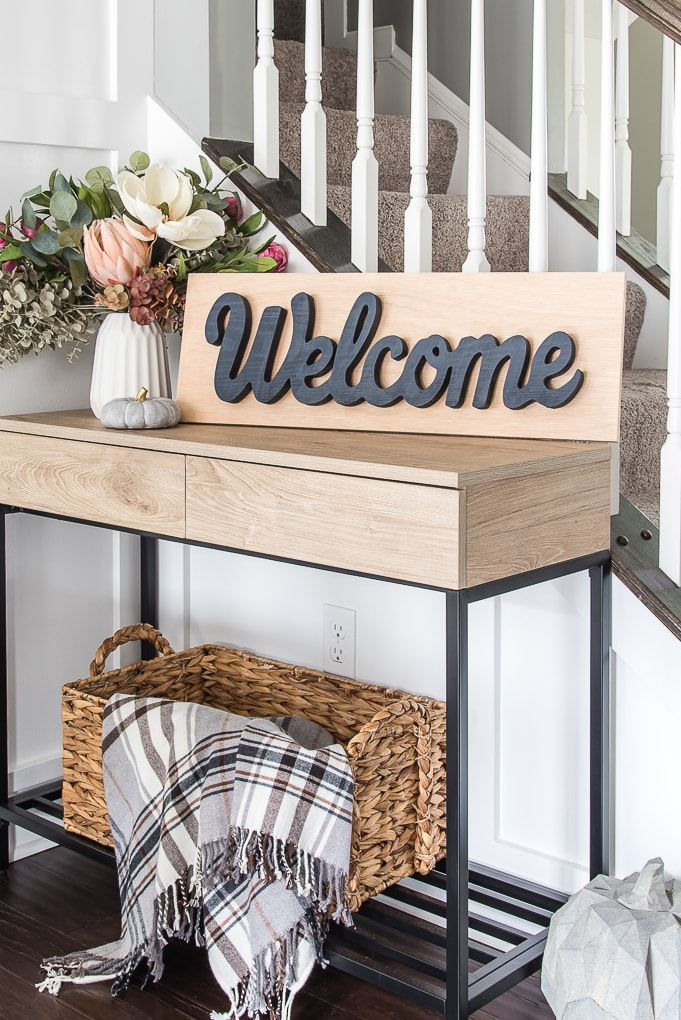dining room side table with welcome sign and floral arrangement
