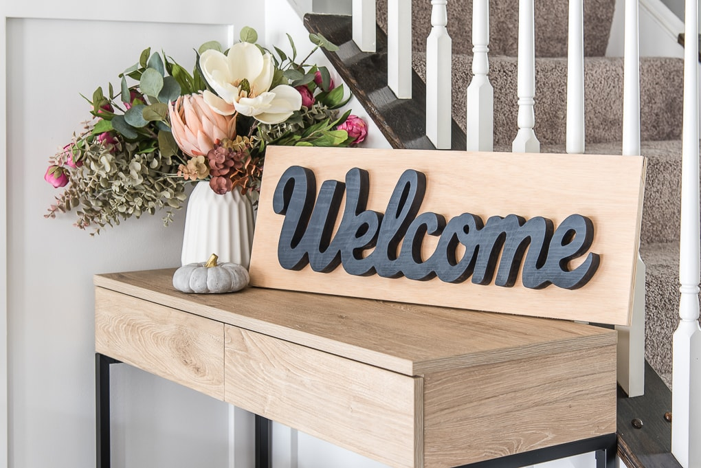 wooden welcome sign on wooden table next to floral arrangement