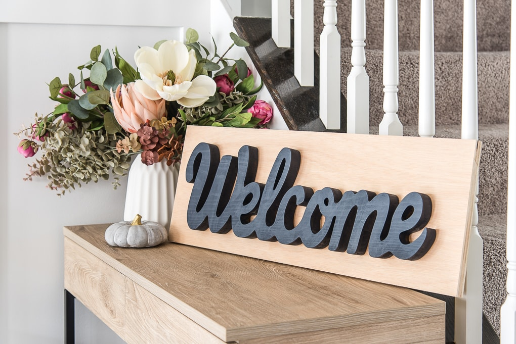 close up of wooden welcome sign on a side table with floral arrangement
