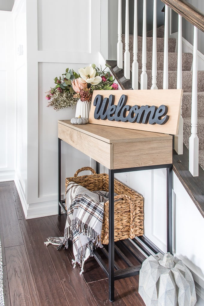 wooden welcome sign on a side table with floral arrangement