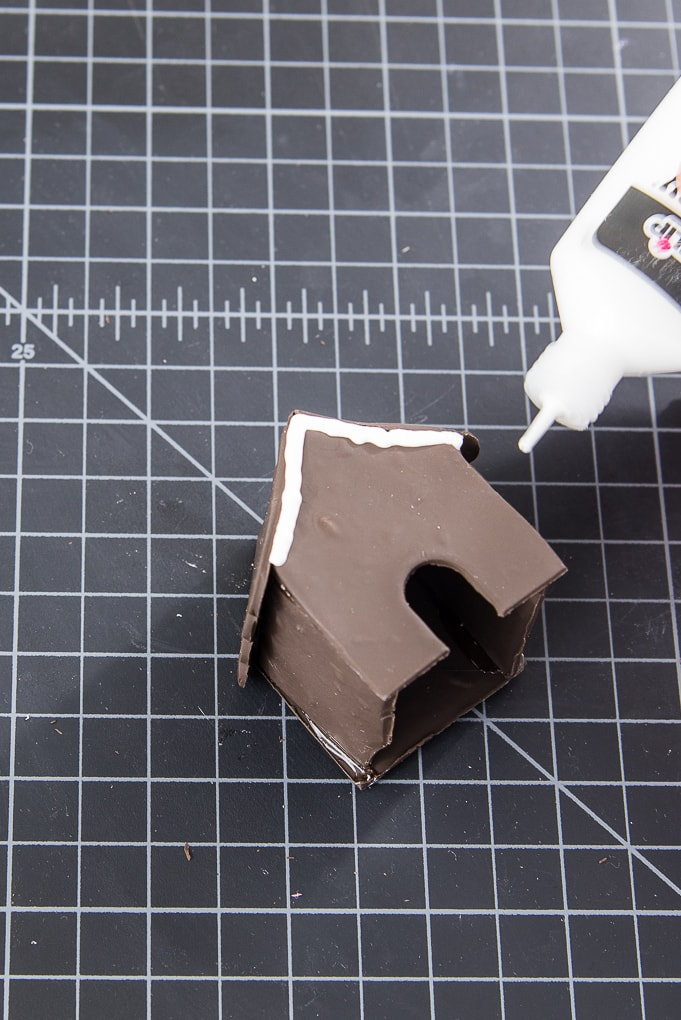 painting a mini gingerbread house using white puffy paint